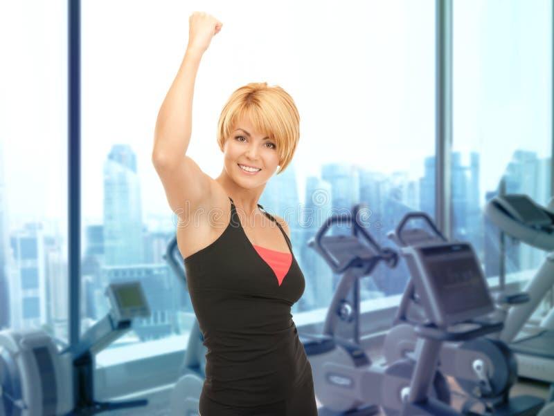 Istruttore felice di forma fisica della donna sopra il fondo della palestra immagini stock