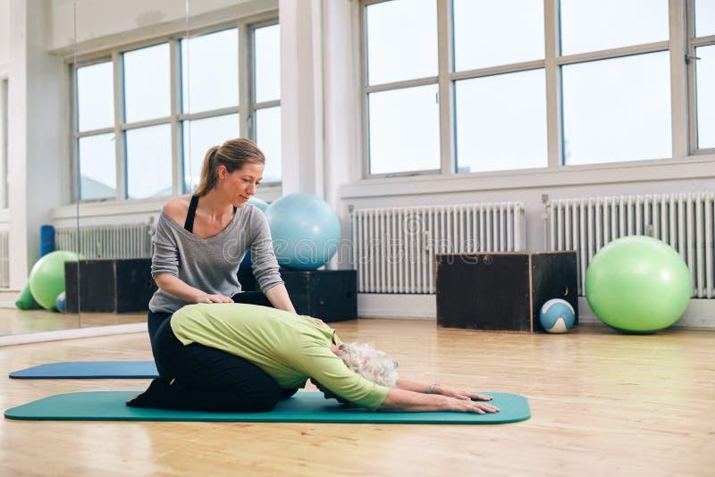 Istruttore femminile che aiuta donna senior che fa yoga immagini stock libere da diritti