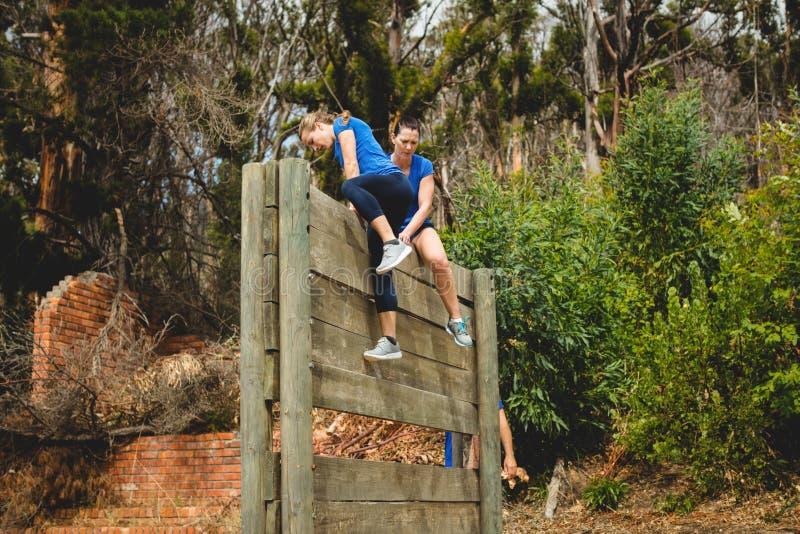 Istruttore femminile che assiste donna per scalare una parete di legno immagini stock