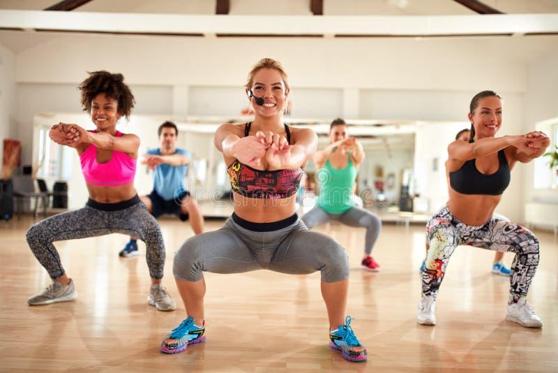 Istruttore femminile che fa gli esercizi per la modellatura culatta e delle coscie fotografie stock