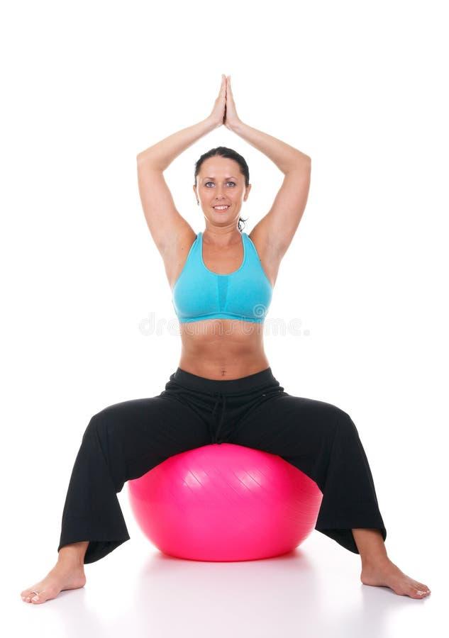 Istruttore femminile di forma fisica che fa yoga sulla palla dei pilates immagini stock libere da diritti