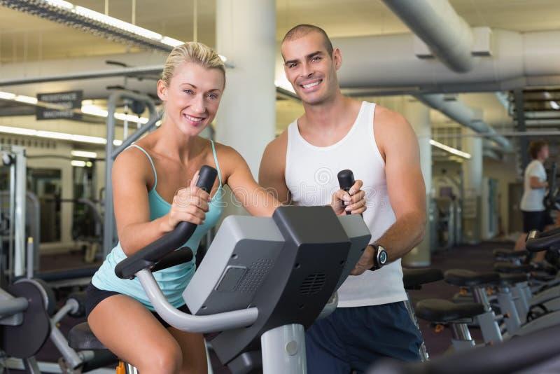 Istruttore maschio che assiste donna con la bici di esercizio alla palestra immagine stock
