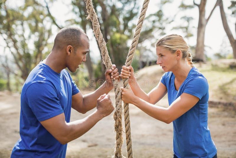 Istruttore maschio che assiste donna nella corda che scala durante la corsa ad ostacoli immagine stock