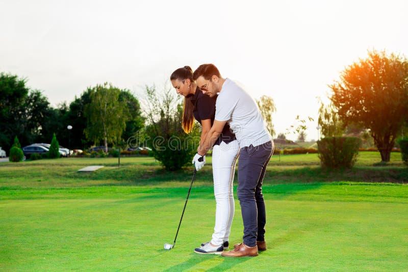 Istruttore maschio che mostra donna per giocare golf fotografia stock libera da diritti
