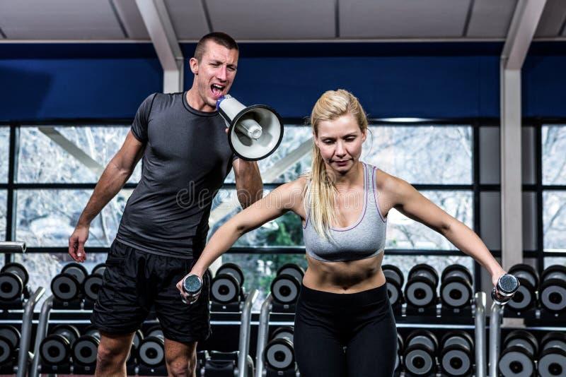 Istruttore maschio che motiva donna adatta con il megafono fotografie stock