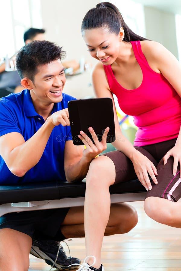 Istruttore personale asiatico con la donna nella palestra di forma fisica immagine stock