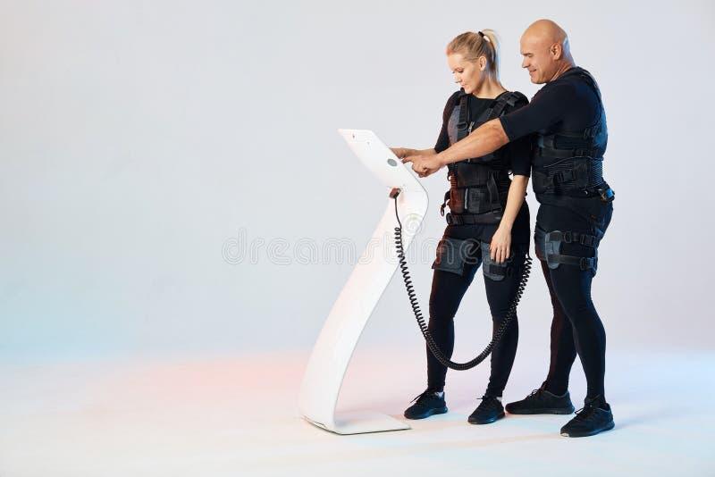 Istruttore personale maschio che impara una bella donna bionda per prepararsi con il dispositivo di SME immagini stock