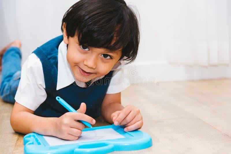 Istruzione di asilo del ragazzo del bambino del bambino che impara il disegno della pittura immagini stock