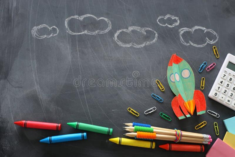 Istruzione Di nuovo al concetto del banco razzo tagliato da carta e dipinto sopra il fondo della lavagna Vista superiore, disposi fotografia stock
