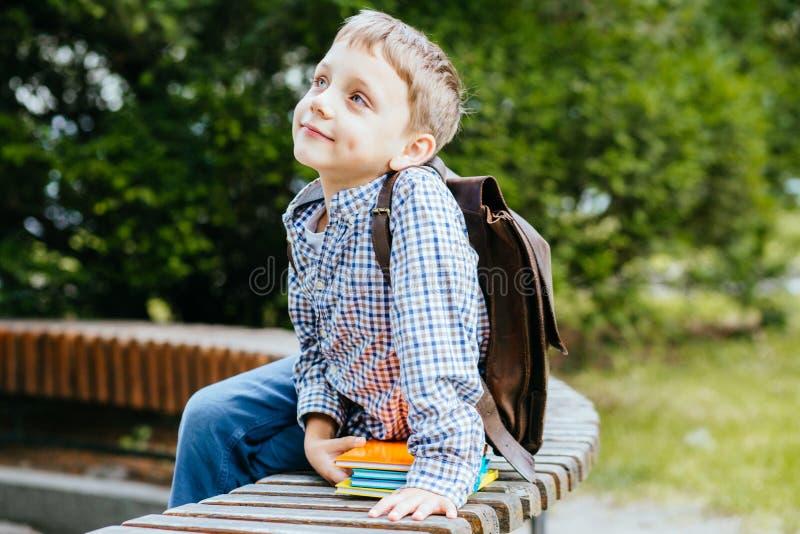 Istruzione e concetto della gente - ragazzo timido dello studente con lo zaino ed i libri variopinti luminosi che si siedono sul  fotografia stock libera da diritti