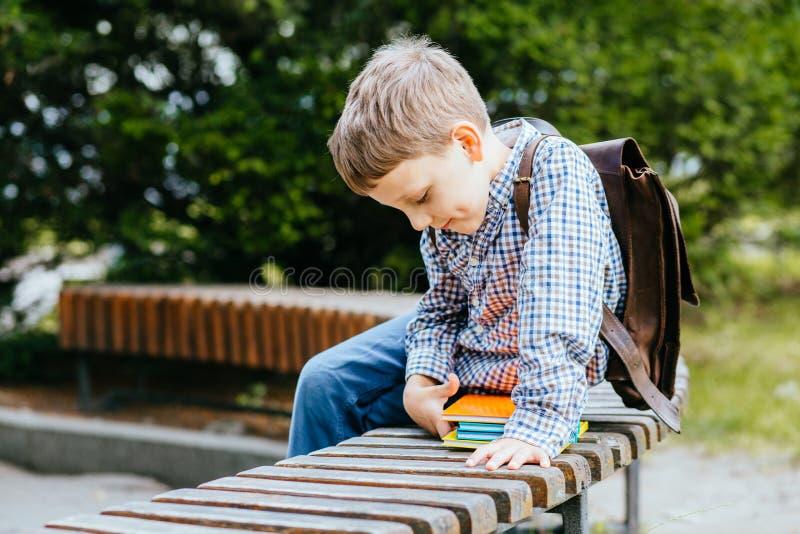 Istruzione e concetto della gente - ragazzo timido dello studente con lo zaino ed i libri variopinti luminosi che si siedono sul  immagine stock