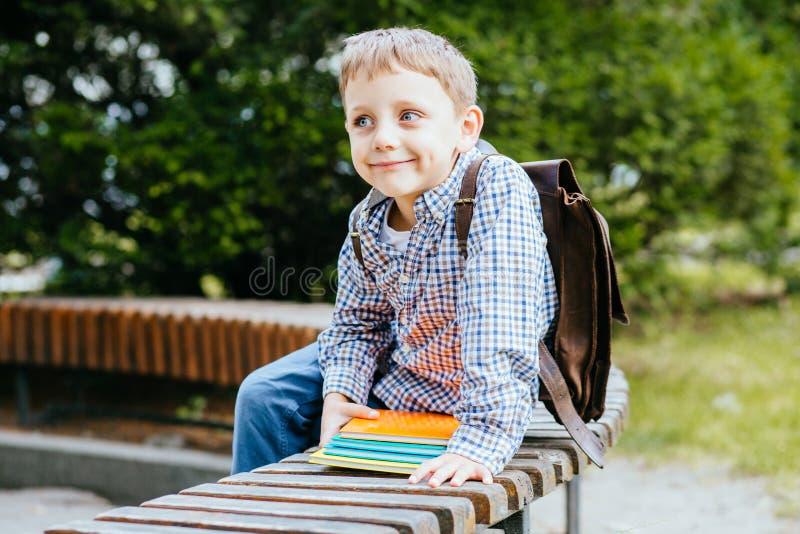 Istruzione e concetto della gente - ragazzo timido dello studente con lo zaino ed i libri variopinti luminosi che si siedono sul  fotografia stock