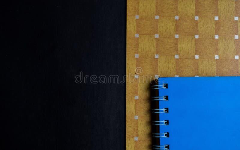 Istruzione e concetto di produttività libri blu, di legno marrone su fondo nero immagine stock libera da diritti
