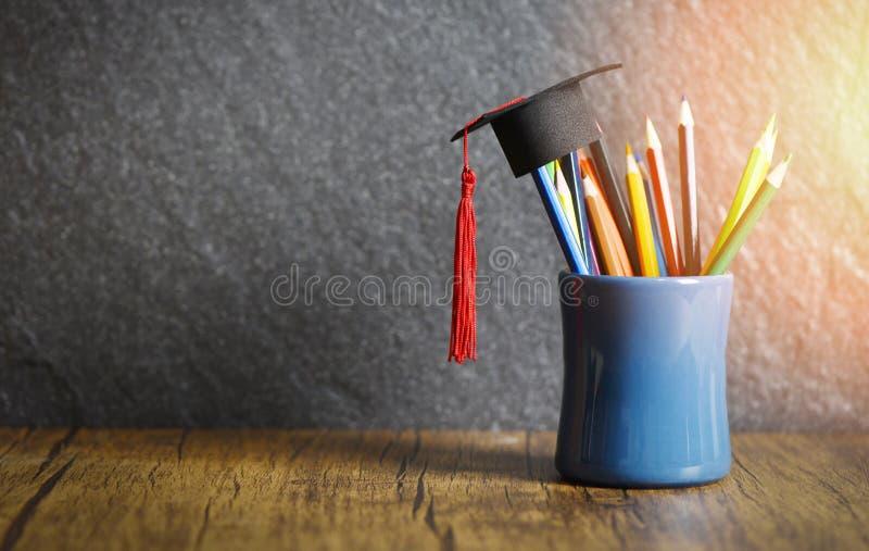 Istruzione e di nuovo al concetto della scuola con il cappuccio di graduazione su colore delle matite in un astuccio per le matit immagini stock