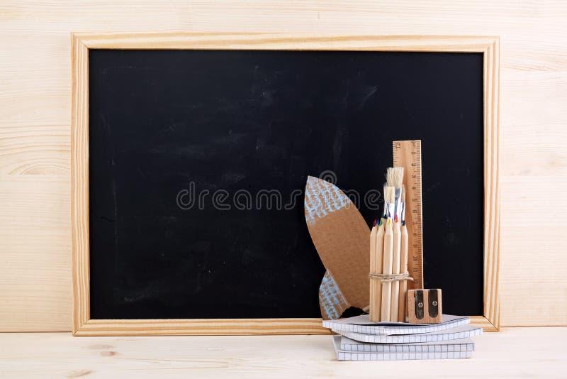 Istruzione o di nuovo al concetto della scuola matite, taccuini sopra il fondo della lavagna immagine stock