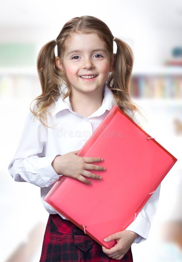 Istruzione scolastica caucasica della cartella della tenuta dell'allievo della ragazza del bambino immagini stock
