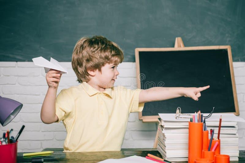 Istruzione scolastica o della casa Allievo con l'aeroplano di carta Bambino del ritratto da scuola elementare fotografia stock libera da diritti
