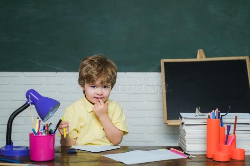 Istruzione scolastica o della casa Bambino del ritratto da scuola elementare Il bambino industrioso sveglio felice sta sedendosi  fotografia stock libera da diritti