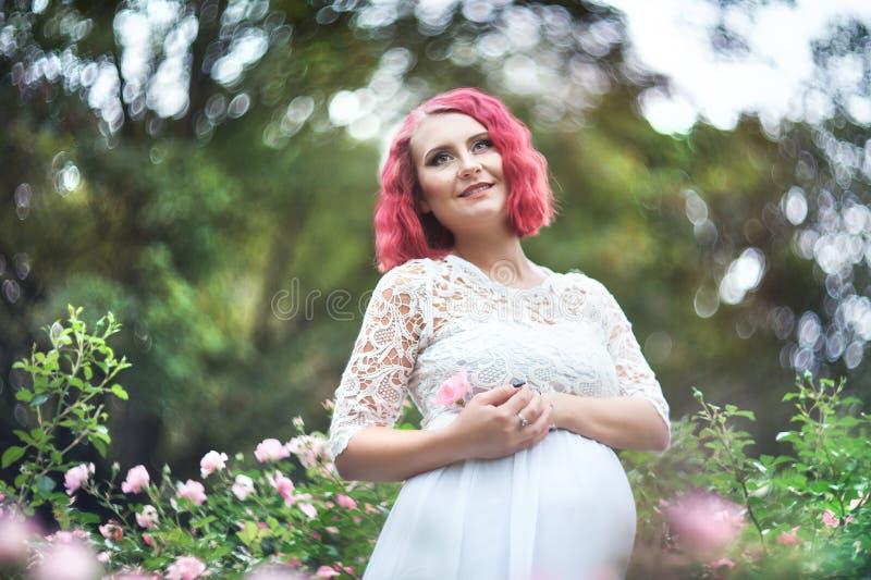 ISTs bonitas novas da mulher que estão no jardim das rosas cor-de-rosa h fotografia de stock