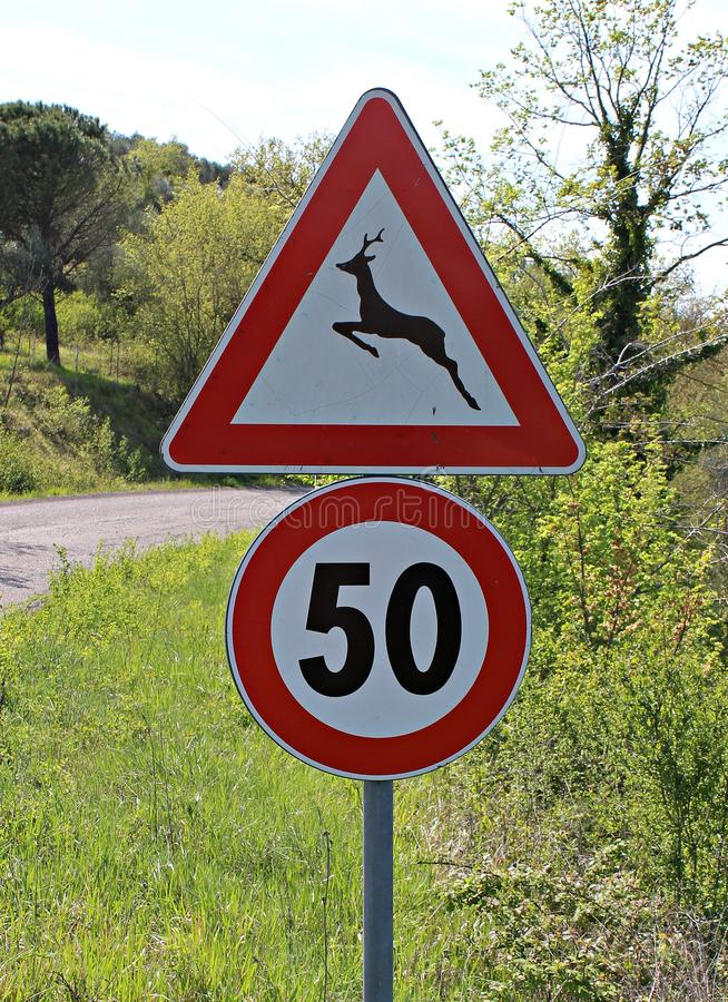 Itália: Animais do perigo do sinal da estrada que cruzam-se e limite de velocidade foto de stock royalty free