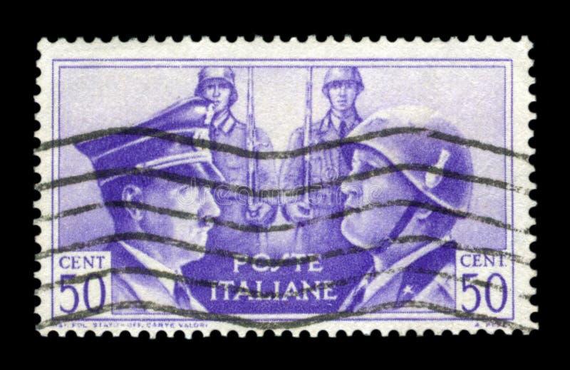 ITÁLIA - CERCA DE 1941: Selo histórico italiano: Fraternidade Alemão-italiana nos braços, nos retratos de Hitler e no Mussolini c foto de stock royalty free