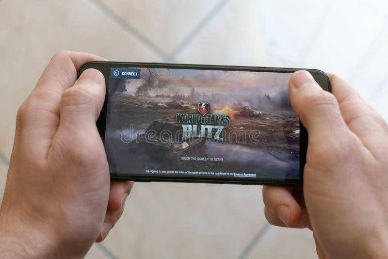 Itália, Roma - 7 de março de 2019: Mãos que guardam um smartphone com o mundo do jogo móvel do raio dos tanques na tela de exposi fotografia de stock royalty free