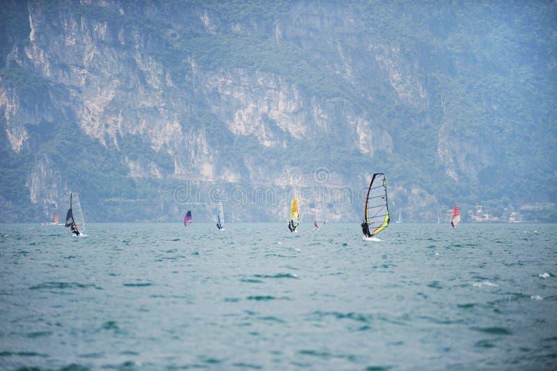 ITÁLIA, TORBOLE, LAGO GARDA, em junho de 2018: Grupo de windsurfers sobre ao norte do lago Garda imagem de stock royalty free