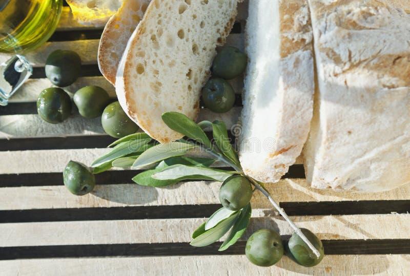 Itália, Toscânia, Magliano, fim acima do pão, das azeitonas e do azeite na placa de desbastamento, vista elevado imagem de stock royalty free