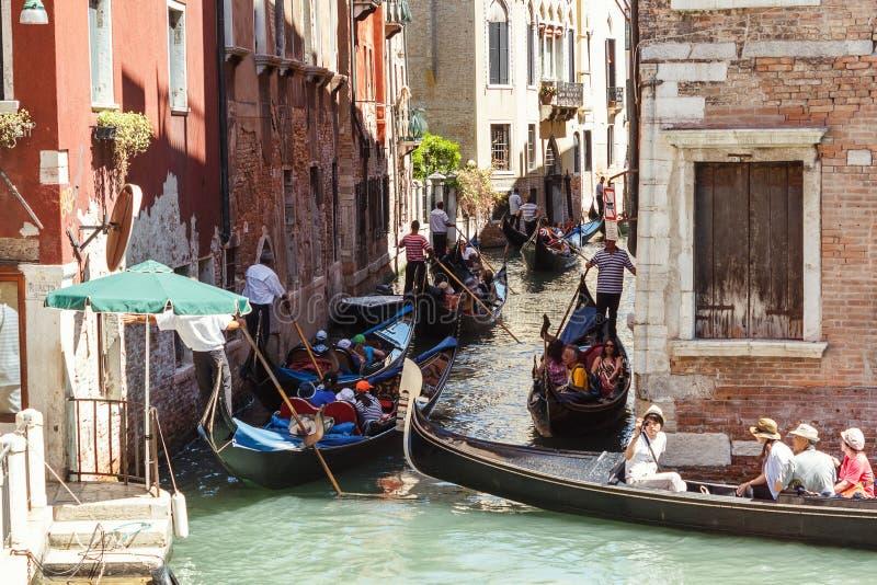 ITÁLIA, VENEZA - EM JULHO DE 2012: Trânsito intenso das gôndola com os turistas que cruzam um canal pequeno o 16 de julho de 2012  fotos de stock