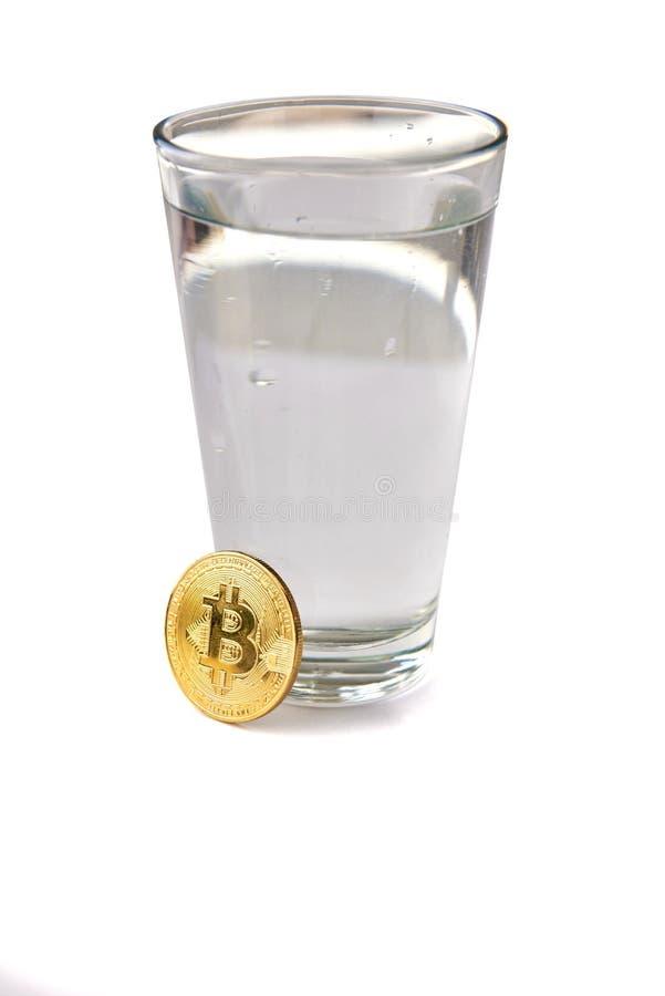 It's di Bitcoin che stanno accanto ad un bicchiere d'acqua Isolato su priorità bassa bianca immagini stock libere da diritti