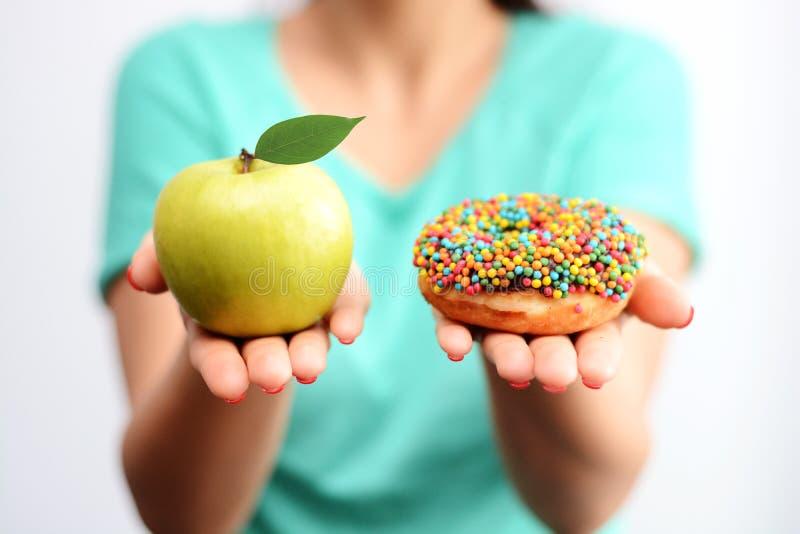 It's dur pour choisir le concept sain de nourriture, avec la main de femme tenant une pomme verte et un beignet de bombe de cal images stock