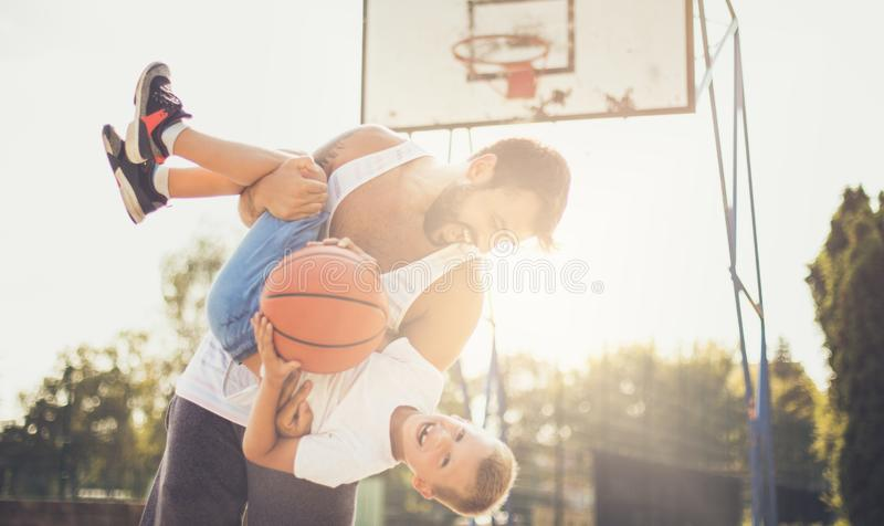 It's important to set aside time for outdoor play. Father and son on basket court. Close up royalty free stock image