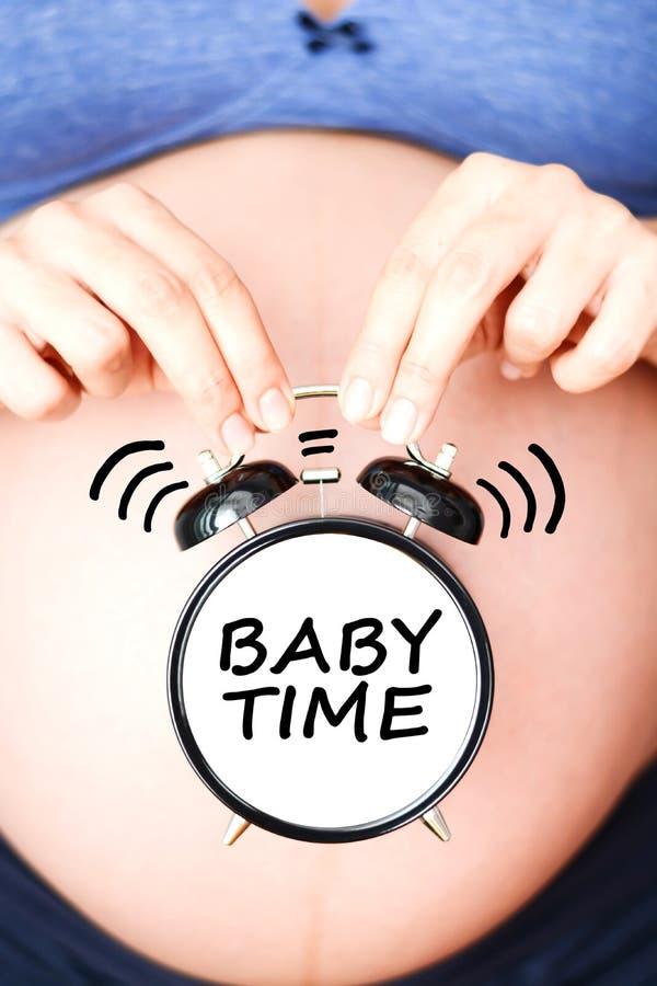 """It's-Zeit, ein Baby mit dem schwangeren Bauch und klassischem Wecker zu haben """"baby time† buchstabierend stockfoto"""