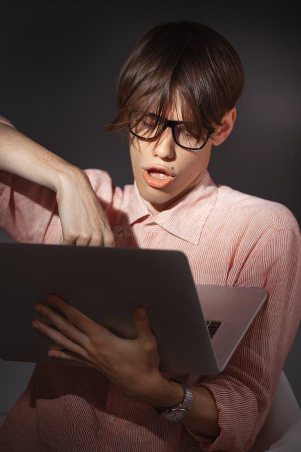 IT计算机书呆子 户内创造性的青少年的millenial画象 有愉快的面孔表示的滑稽的年轻人在玻璃拥抱 免版税库存照片