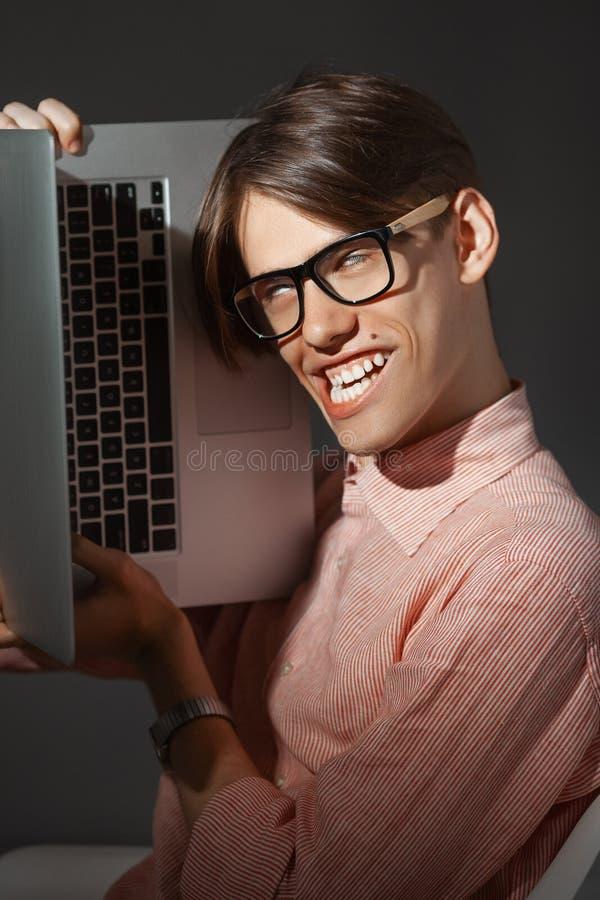 IT计算机书呆子 户内创造性的青少年的millenial画象 有愉快的面孔表示的滑稽的年轻人在玻璃拥抱 库存照片