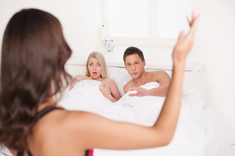 Its not what you think!. Rear view of young women gesturing while Her boyfriend lying on the sofa with another women royalty free stock photo
