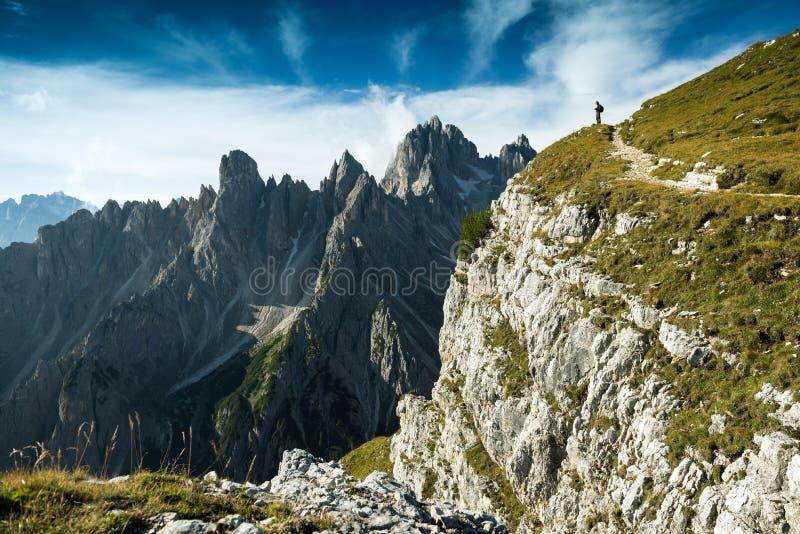 Italië, Dolomiet - Mensenwandelaar die zich zeer verre van de rand van de onvruchtbare rotsen bevinden stock foto's