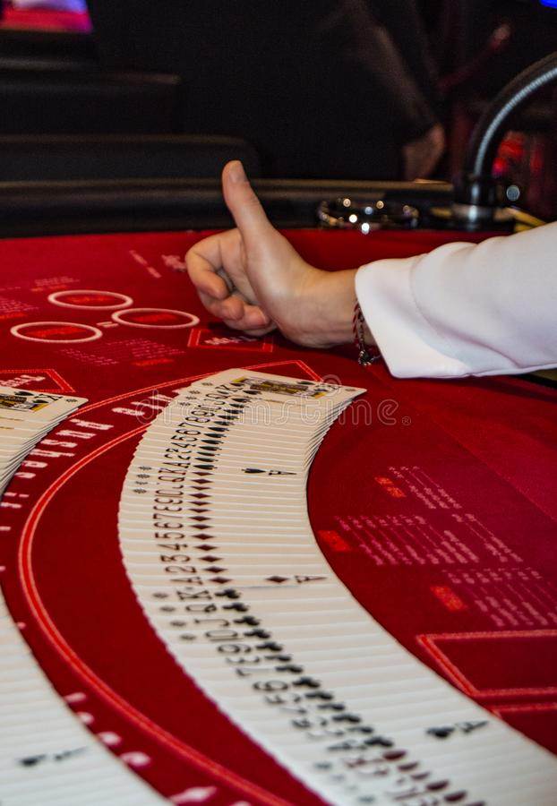 Italië - 11 Oktober, 2018, de handelaar legt een speelkaart op de lijst met rode doek in een casinodoctorandus in de exacte weten royalty-vrije stock afbeelding