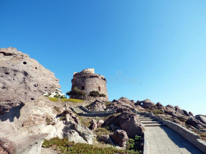 Italië, Sardinige, Portoscuso, promenade met mening van oude Spaanse watchtower royalty-vrije stock afbeelding