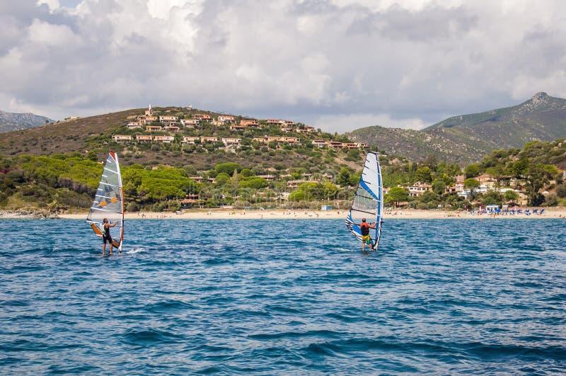 ITALIË tweepersoonswindsurfing Sardinige op blauw water voor rotsachtige kust stock foto