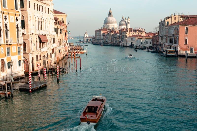 Italië, Venetië 09 Februari 2019: de boten varen in het grote kanaal van Venetië tijdens een zonnige dag met sommige gondels aan  royalty-vrije stock afbeelding