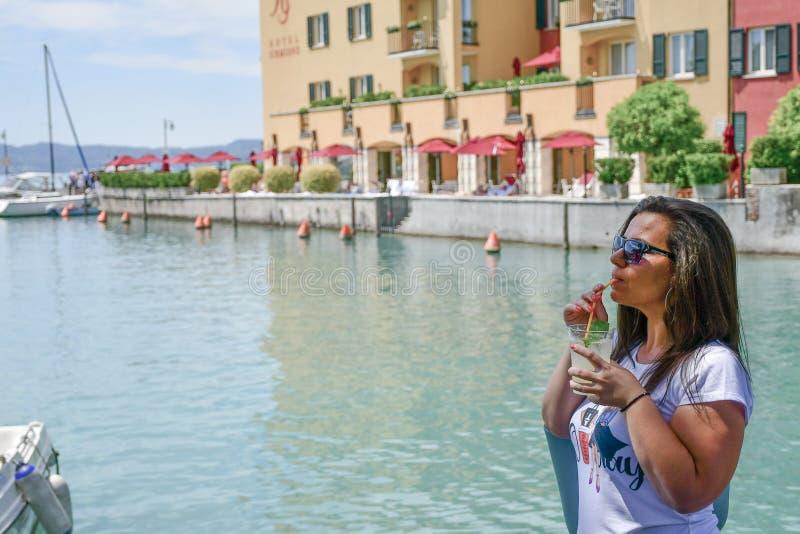Itali? Glimlachende vrouw die Ijskoude limonade op Garda-meer drinken royalty-vrije stock fotografie