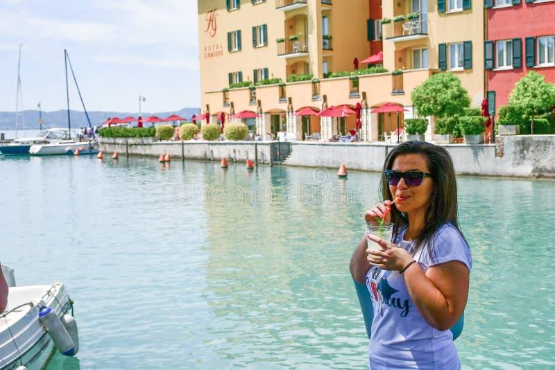 Itali? Glimlachende vrouw die Ijskoude limonade op Garda-meer drinken stock afbeeldingen