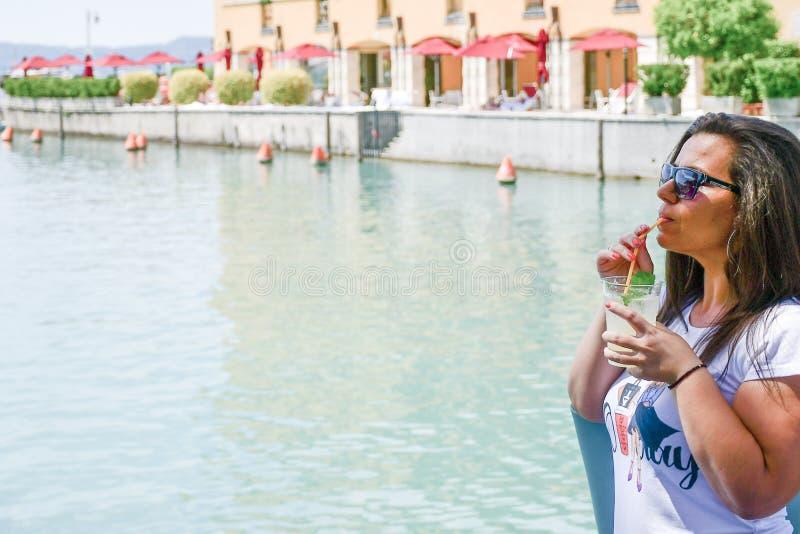 Itali? Glimlachende vrouw die Ijskoude limonade op Garda-meer drinken royalty-vrije stock foto