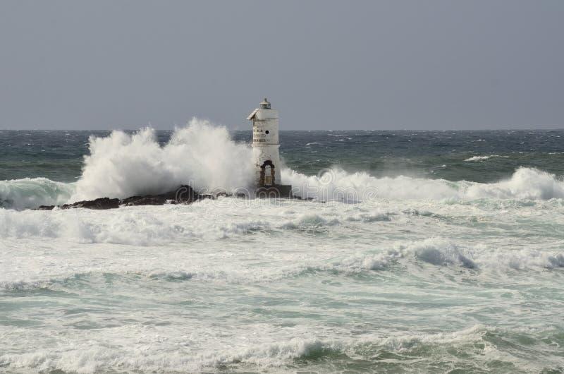 Italia, ` de Mangiabarche del `, tormenta Las ondas rompen contra el faro o el faro imagenes de archivo
