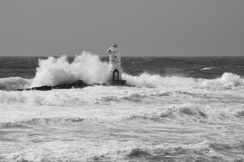 Italia, ` de Mangiabarche del `, tormenta Las ondas rompen contra el faro o el faro foto de archivo