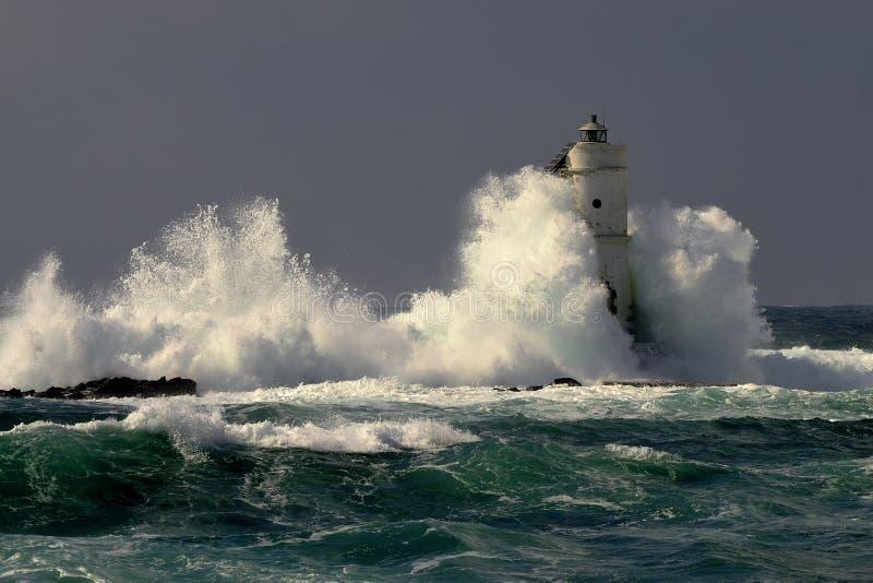 Italia, ` de Mangiabarche del `, tormenta Las ondas rompen contra el faro o el faro fotos de archivo