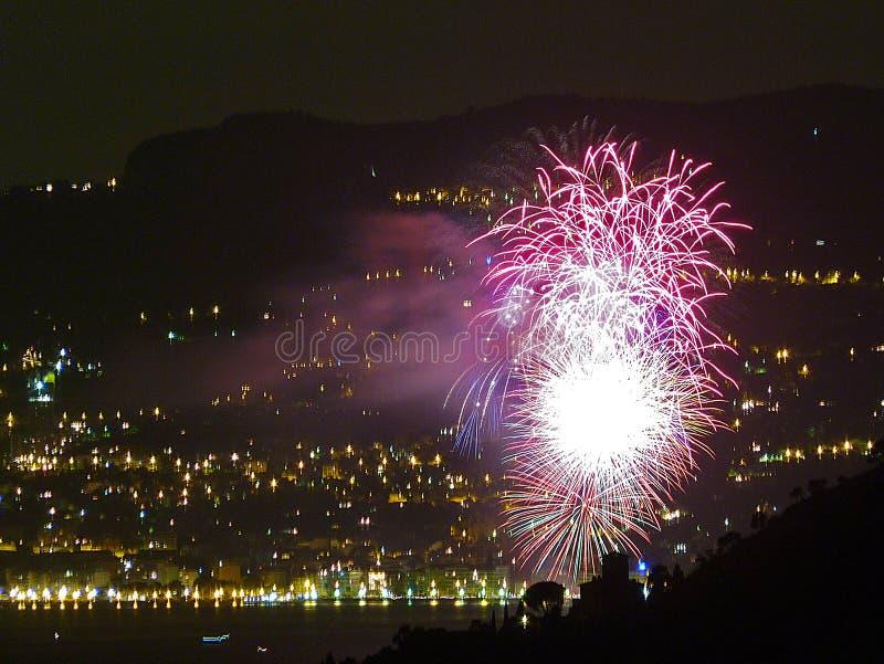 Italia, Liguria, Ventimiglia, fuegos artificiales, en el fondo las luces de Monte Carlo imágenes de archivo libres de regalías
