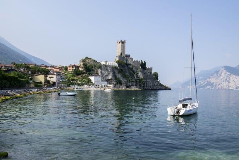 ITALIA, MALCESINE - 11 de junio, estación turística en el lago Garda, la opinión del castillo de Malcesine con el barco y Malcesi foto de archivo libre de regalías