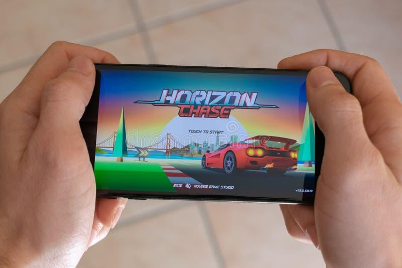 Italia, Roma - 7 de marzo de 2019: Manos que sostienen un smartphone con el juego móvil de la caza del horizonte en la pantalla d fotografía de archivo